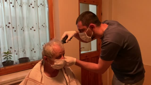 vídeos de stock e filmes b-roll de son cutting his father's hair, covid 19 quarantine - covid hair