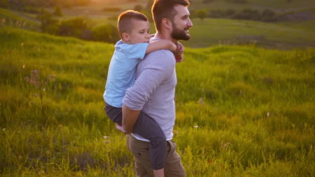vidéos et rushes de père embrassant fils assis sur son dos en marchant dans le champ - chrono sport