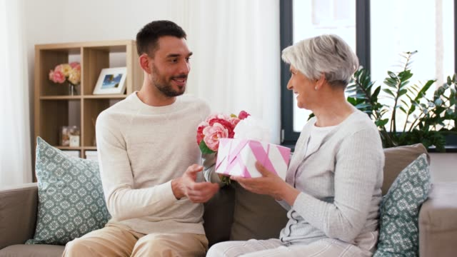 son giving present and flowers to senior mother family, mother's day and birthday concept - smiling adult son giving present and flowers to his senior mother at home mothers day stock videos & royalty-free footage