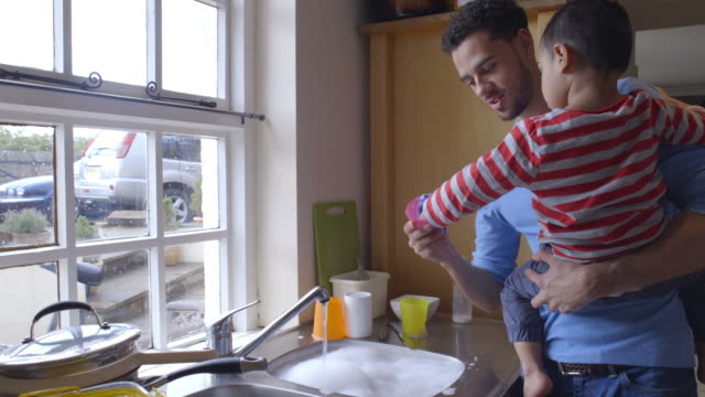 Son Helping Father To Wash Dishes In Kitchen Sink video