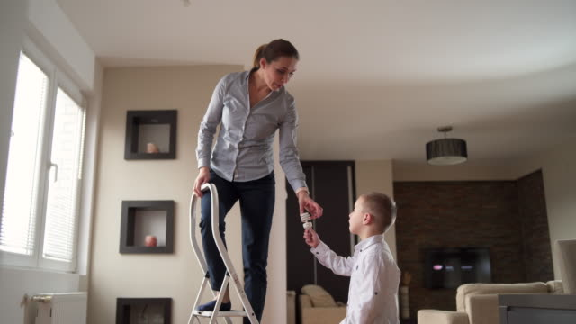 Son helping mother to change a lightbulb