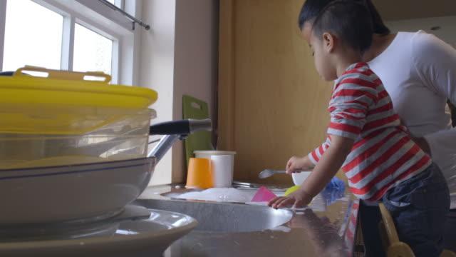 vídeos de stock, filmes e b-roll de filho de mãe ajudando lavar pratos no cozinha pia - afazeres domésticos
