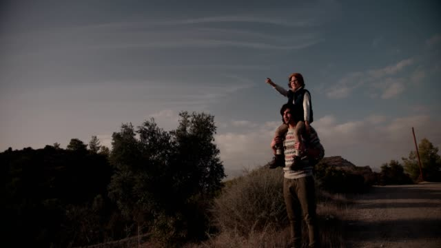 son on father's shoulders looking at view during mountain hiking - viaggiare zaino in spalla video stock e b–roll
