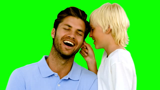 Son pinching the ear of his father on green screen video