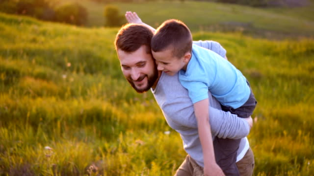 sonen sitter på far tillbaka spelar som flygplan - skägg bildbanksvideor och videomaterial från bakom kulisserna