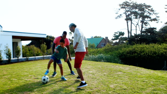 Son tackling father and grandfather while playing soccer video