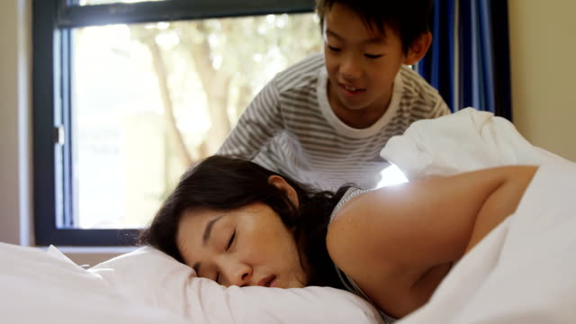 Son waking up his mother in bedroom 4k video