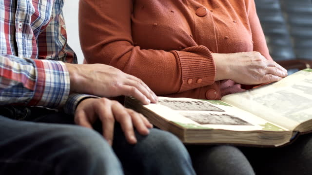 Son with an elderly mother watching old photo album