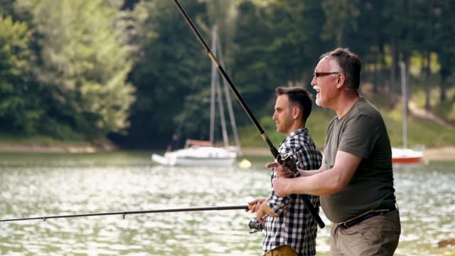 son with father fishing at sunny day - łowić ryby filmów i materiałów b-roll