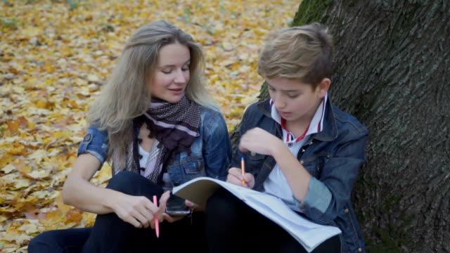 son med mor göra läxor tillsammans sitter på hösten lämnar i park - linjerat papper bakgrund bildbanksvideor och videomaterial från bakom kulisserna