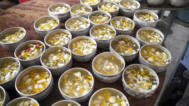 vídeos de stock, filmes e b-roll de songkarn festival, água para escultura de buda com pólen de flores - ano novo budista