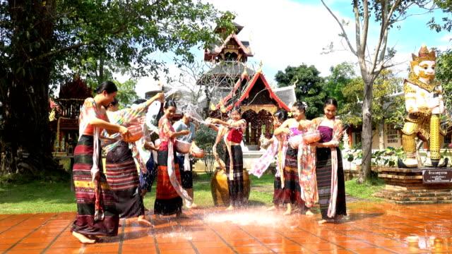 vídeos de stock, filmes e b-roll de festival de songkran-mulheres bonitas desgastam o traje tailandês do traditionnel que espirra a água em homens no templo no dia de songkran-4k - ano novo budista