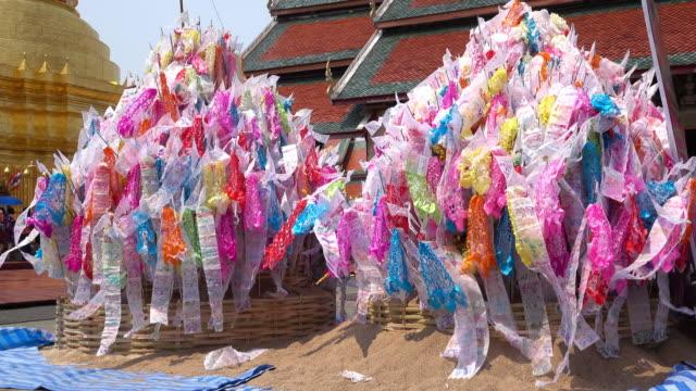 vídeos de stock, filmes e b-roll de songkran festival na tailândia, a tradicional decoração na areia bandeira destaque em wat pará que hariphunchai em lamphun - ano novo budista