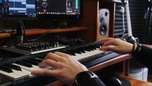 vidéos et rushes de ingénieur musicien auteur-compositeur jouant du piano à clavier midi dans le studio d'enregistrement à domicile avec des moniteurs mêlant équipement et guitare. studio de musique d'enregistrement à domicile. - synthétiseur