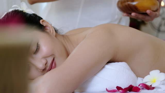 vídeos y material grabado en eventos de stock de sofisticado tratamiento de spa y masaje de relajación, mujer joven recibir piedras calientes spa de espalda - tratamiento de spa