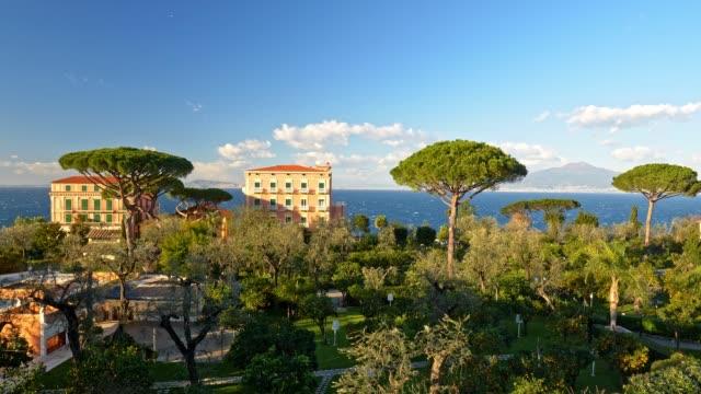 Sorrento, Italy. View of Vesuvius volcano. Villas on coast Tyrrhenian (Mediterranean) Sea. Park with rich green flora. Panning shot