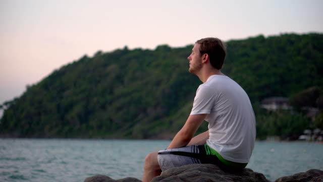 vídeos y material grabado en eventos de stock de triste triste joven sentado junto a la playa tropical mirando al océano - luchar
