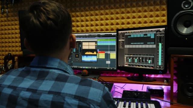 ljudtekniker skapar sång i professionell inspelningsstudio. musiker som arbetar hemma studio med bildskärmar och equalizer blandning redskap på skärmen. komponera musikprocess - studiofotografi bildbanksvideor och videomaterial från bakom kulisserna