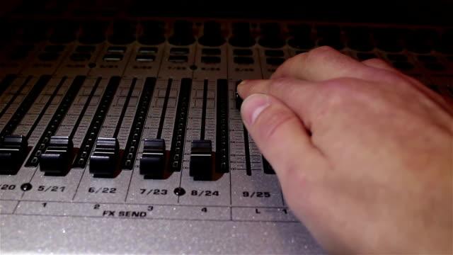 vidéos et rushes de l'ingénieur du son abaisse les curseurs des pistes sonores du mixeur sonore, étournant le son. - batteur électrique