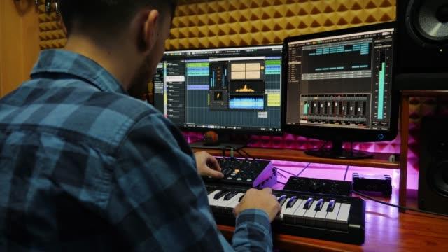 vidéos et rushes de producteur sonore créant des chansons pop rock avec moniteurs et vitesse de mixage d'égaliseur à l'écran. ingénieur du son mixant et maîtrisant au studio de musique son. poste de travail audio numérique. studio d'enregistrement à domicile - synthétiseur