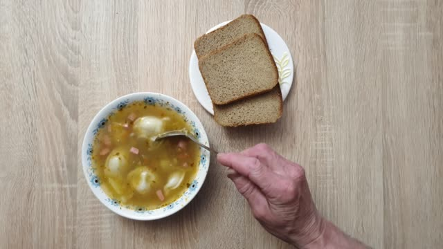 Soup in the plate. Bread and soup. Spoon in a bowl of soup.