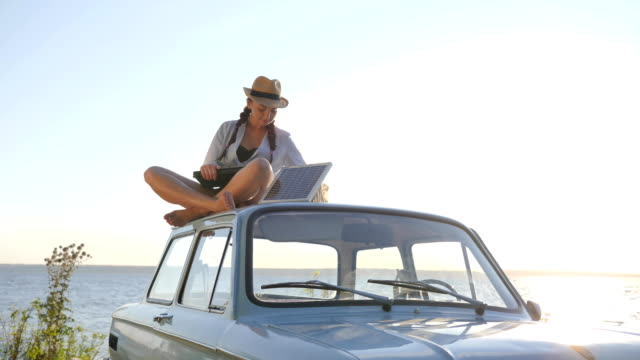 sources of natural power, girl sits on roof blue antique car with solar array and laptop in open air, female sitting on vintage car video
