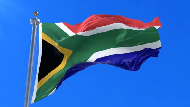 South Africa flag waving at wind in slow in blue sky, loop video