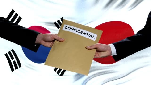 vídeos de stock, filmes e b-roll de funcionários da coréia do sul e japão trocando envelope confidencial, contra bandeiras - coreia