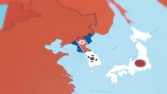vidéos et rushes de corée du sud, corée du nord avec un drapeau national sur la carte du monde - nord