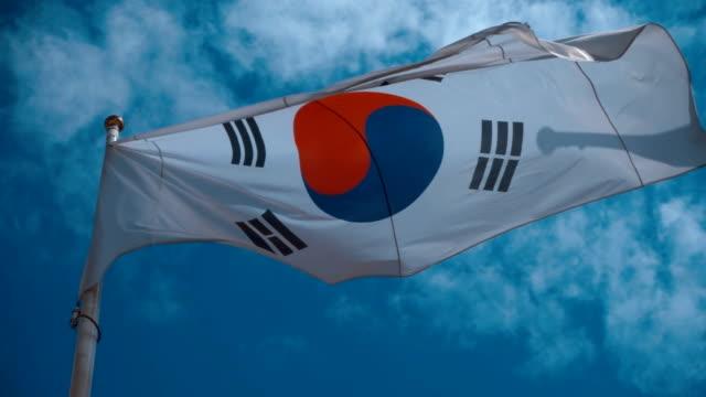 mavi gökyüzü karşı rüzgarda sallayarak bayrak direğine güney kore bayrağı - güney kore stok videoları ve detay görüntü çekimi