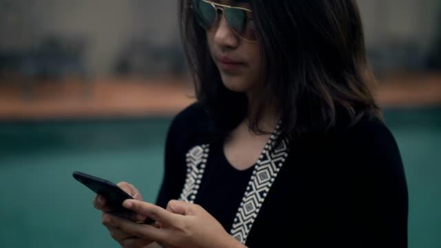 southeast asia : businesswoman using phone in the garden - 40 49 lat filmów i materiałów b-roll
