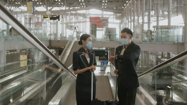 Southeast Asian cabin crew couple at the airport-stock video video