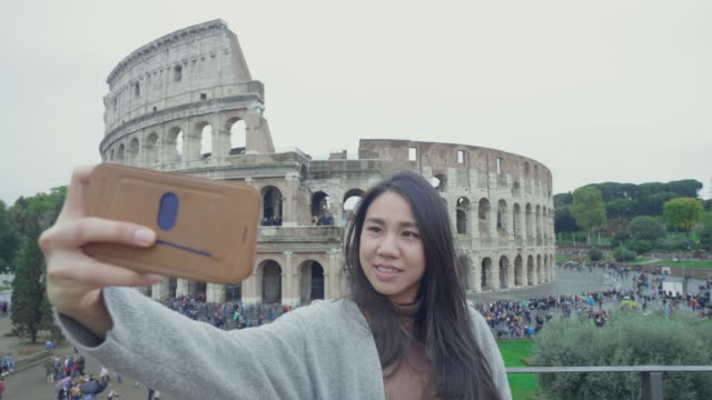 Southeast asian couple take a sight seeing and selfie in front of Colosseum, Italy