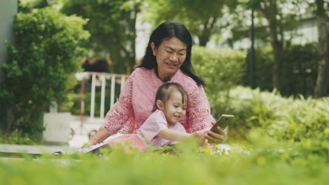 southeast asian family consist of grandmother and her niece are using smart phone for relaxation at the garden - 50 59 lat filmów i materiałów b-roll