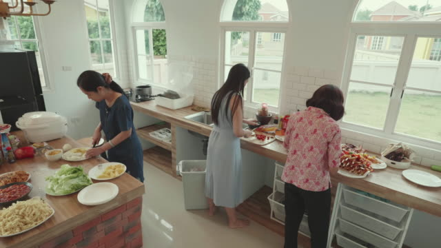 Southeast asian family prepare dinner together by cooking in domestic kitchen during Summer holidays