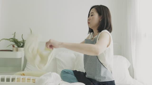 週末にその布を折り畳み東南アジア女性 - 楽しい 洗濯点の映像素材/bロール