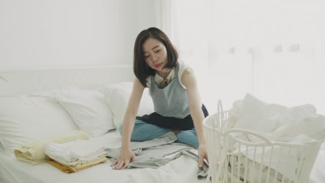 Southeast Asian woman folding their cloth on weekend