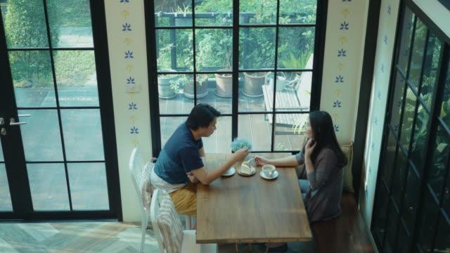 コーヒーカフェでくつろぐ東南アジアの若いカップル - カフェ文化点の映像素材/bロール