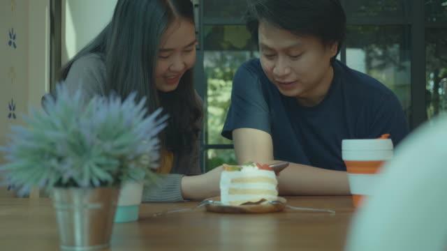 コーヒーカフェで一緒に携帯電話を見ている東南アジアの若いカップル - カフェ文化点の映像素材/bロール