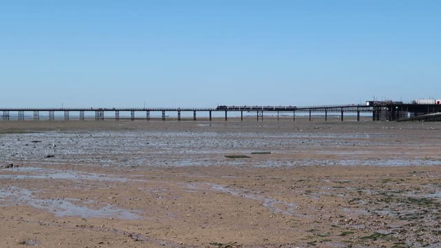 Southend pier with electric train or tram moving slowly along it. Outdoors on a summers day.ram