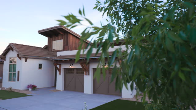 vídeos de stock e filmes b-roll de southwest white home angled reveal from tree - driveway, no people