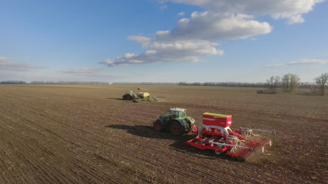 Sowing campaign in early spring. Three tractors pull seeders, aerial 4K video video