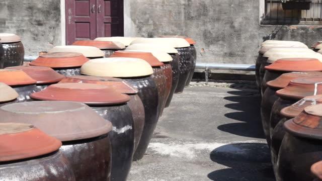 di soia fermentato in una pentola di argilla di salsa di soia - fermentare video stock e b–roll