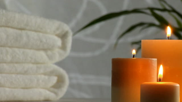 Spa BG: Flickering Candles, Towels & Bamboo Candles flicker in the foreground in front of fluffy white towels. Green leafy bamboo and a white curtian billow in the background. candle stock videos & royalty-free footage