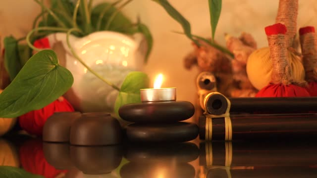 spa-zusammensetzung brennende kerzen, steine für die körpermassage, aromatische kräuter und tasse für teezeremonie. schließen sie die massagedekoration mit kerzen und steinen im beauty-spa. zen und relax-konzept - sauna und nassmassage stock-videos und b-roll-filmmaterial