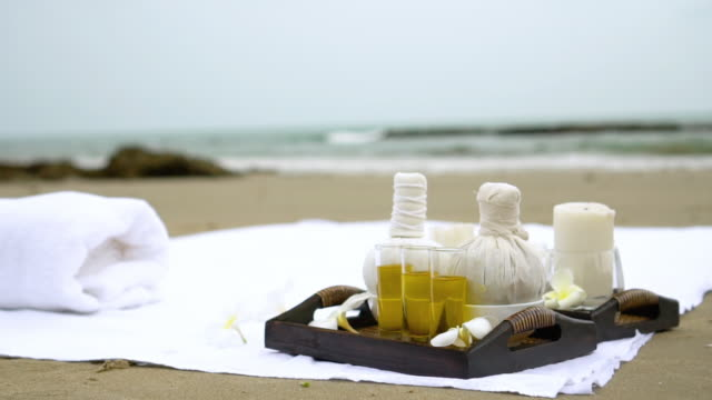 Spa equipment on beach Essential oil , Beach towel with sea on background massage oil stock videos & royalty-free footage