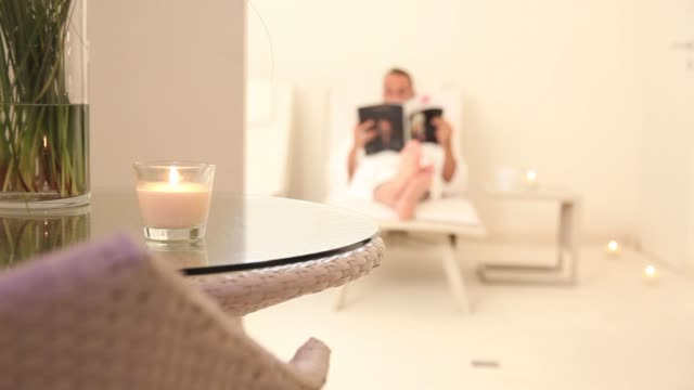 spa interior with small candle and blurred man reading a magazine on a beach video