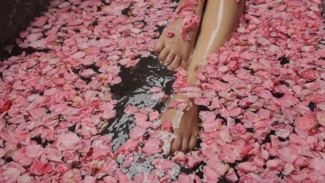 spa, legs of unrecognizable woman enjoying bath with flower petals - aromaterapia video stock e b–roll