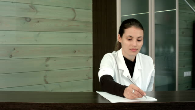 Spa manager filling in form and greeting customers at the reception desk video