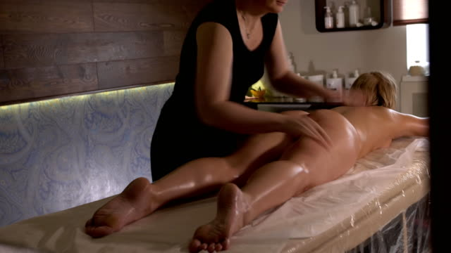vídeos de stock e filmes b-roll de spa massage. aromatherapy oil massage. masseur doing aromatherapy oil massage on beautiful young healthy caucasian woman body in spa salon - massajar